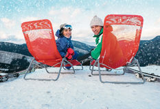 Two smiling skiers sit in chaise-longue on the mountain top Stock Photos
