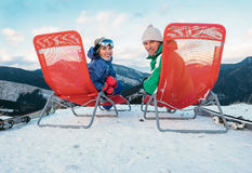 Two smiling skiers sit in chaise-longue on the mountain top royalty free stock image