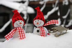 Two smiling snowmen friends in the snow Stock Image