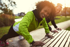 Two smiling sportswomen doing push-ups. Using bench in park Royalty Free Stock Photo