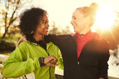 Two smiling sportswomen hugging while standing outdoors Stock Photo