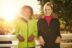 Two smiling sportswomen leaning on bridge and looking at camera Royalty Free Stock Photos