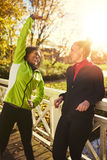 Two smiling sportswomen stretching on bridge Royalty Free Stock Photography