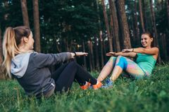 Two smiling sportswomen training outdoors doing full sit-ups sitting opposite each other on grass in forest.  Stock Image