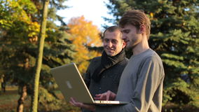 Two smiling startup businessmen discussing sharing laptop computer outdoors in the park at autumn stock video