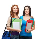 Two smiling students with bag, folders and tablet Stock Photos