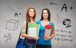 Two smiling students with bag, folders and tablet Stock Image
