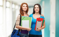 Two smiling students with bag, folders and tablet Royalty Free Stock Photos