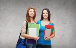 Two smiling students with bag, folders and tablet Stock Photo