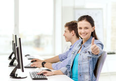 Two smiling students in computer class. Education, gesture, technology and school concept - two smiling students in computer class and girl showing thumbs up Stock Photo