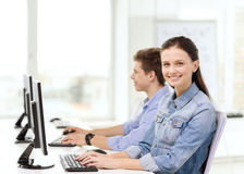 Two smiling students in computer class. Education, technology and school concept - two smiling students in computer class Stock Images