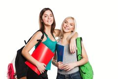 Two smiling students girl with school bags on. Two smiling students friends with copybooks posing isolated on white background Royalty Free Stock Photography