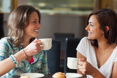 Two smiling students having a cup of coffee. In college canteen Stock Image