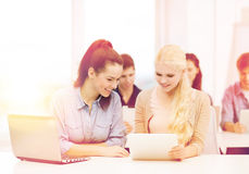 Two smiling students with laptop and tablet pc. Education, technology and internet concept - two smiling students with laptop computer, tablet pc and notebooks Stock Photo