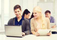 Two smiling students with laptop and tablet pc Royalty Free Stock Photos
