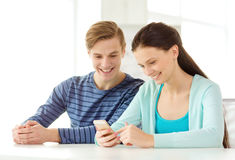Two smiling students with smartphone at school Royalty Free Stock Image