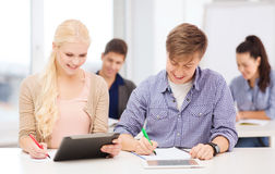 Two smiling students with tablet pc and notebooks Stock Photos