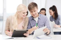 Two smiling students with tablet pc and notebooks Stock Image