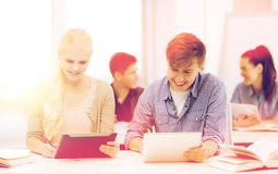 Two smiling students with tablet pc at school. Education, technology and internet concept - two smiling students with tablet pc, notebooks and books at school royalty free stock photography