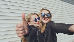 Two smiling stylish girls in leather jackets and sunglasses show a gesture of thumbs up. Background of white horizontal. Rolling shutters stock video footage