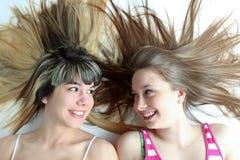 Two smiling teen girls. Having fun with long hair Royalty Free Stock Image