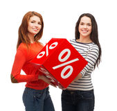 Two smiling teenage girl with percent sign on box Stock Image
