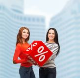 Two smiling teenage girl with percent sign on box Stock Photos