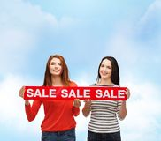 Two smiling teenage girl with percent sign on box Royalty Free Stock Photo