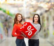Two smiling teenage girl with percent sign on box Stock Images