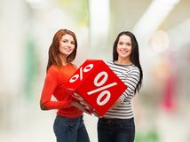 Two smiling teenage girl with percent sign on box Royalty Free Stock Photography