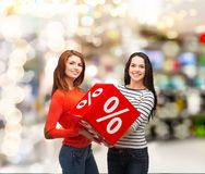 Two smiling teenage girl with percent sign on box Royalty Free Stock Photos