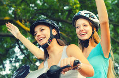 Two smiling teenage girlfriends riding scooter on sunny summer d Royalty Free Stock Photos