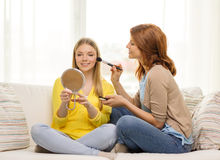 Two smiling teenage girls applying make up at home Stock Photos