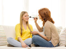 Two smiling teenage girls applying make up at home Royalty Free Stock Photo