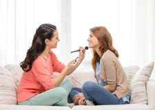 Two smiling teenage girls applying make up at home Stock Image