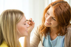 Two smiling teenage girls applying make up at home Stock Photo