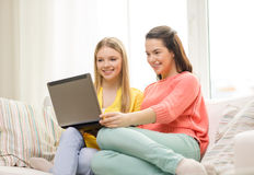 Two smiling teenage girls with laptop at home Royalty Free Stock Images