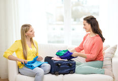 Two smiling teenage girls packing suitcase at home Stock Photos
