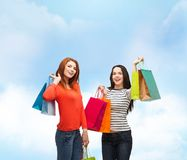 Two smiling teenage girls with shopping bags Stock Images