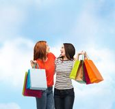 Two smiling teenage girls with shopping bags Stock Photos
