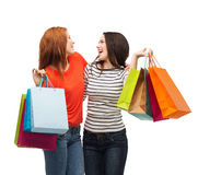 Two smiling teenage girls with shopping bags Royalty Free Stock Photos