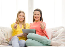 Two smiling teenage girls with tablet pc at home Royalty Free Stock Image