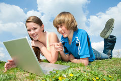 Two Smiling teenagers with laptop Royalty Free Stock Photography