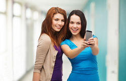 Two smiling teenagers with smartphone Royalty Free Stock Image
