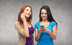 Two smiling teenagers with smartphones Stock Photography