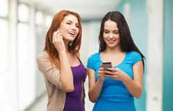 Two smiling teenagers with smartphones Royalty Free Stock Photos
