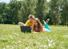 Two smiling teenagers students with laptop resting on meadow. Education. Technology. Boy and girl sitting on grass with laptop, online in park. Two smiling Royalty Free Stock Photography