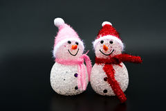 Two smiling toy christmas snowman on black Royalty Free Stock Photography