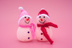 Two smiling toy christmas snowman on pink. Background Royalty Free Stock Images