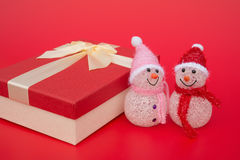 Two smiling toy christmas snowman and a present box on red Royalty Free Stock Photos